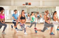 Eignungsgruppe in der Turnhalle, die Aerobic-Übungen tut Stockfotografie