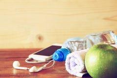 Eignungskonzept mit Flasche Wasser, Handy mit Kopfhörern Lizenzfreies Stockfoto