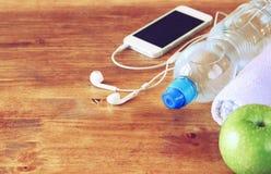 Eignungskonzept mit Flasche Wasser, Handy mit Kopfhörern Lizenzfreie Stockfotos