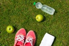 Eignungskonzept, rosa Turnschuhe, Notizbuch mit Bleistift, Äpfel und Flasche Wasser auf grünem Gras draußen, Draufsicht Lizenzfreie Stockfotos