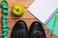 Eignungskonzepte - tragen Sie Kleidung mit Früchten zur Schau und Notizbuch, flehen an Lizenzfreie Stockfotografie