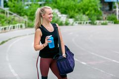 Eignungslebensstil Junge Frau, die eine Wasserflasche und eine Tasche auf ihrer Schulter nach einem Training hält Training am Sta stockfotografie