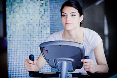 Eignungsmädchen arbeitet mit Stepper aus Starker Brunette mit dem gelockten Haar, das Aerobic auf Stepper tut Stockbilder