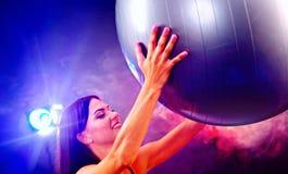 Eignungsmädchen, das in der Turnhalle mit fitball trainiert Stockbild