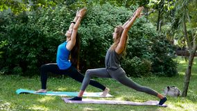 Eignungsmädchen, die draußen Yoga Virabhadrasana tun stockfotografie