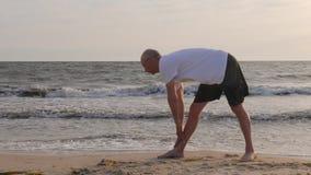 Eignungsmanntraining, das Übung auf sandigem Ufer auf Seelandschaft ausdehnt stock video footage