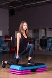 Eignungsschritt, Training, Aerobic, Sportkonzept - athletischer Frauentrainer am Schritthandeln aerob mit Steppers zuhause Lizenzfreie Stockfotos