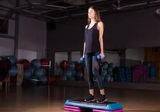 Eignungsschritt, Training, Aerobic, Sportkonzept - athletischer Frauentrainer am Schritthandeln aerob mit Steppers zuhause Lizenzfreie Stockfotografie
