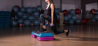 Eignungsschritt, Training, Aerobic, Sportkonzept - athletischer Frauentrainer am Schritthandeln aerob mit Steppers zuhause Lizenzfreies Stockbild