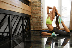Eignungstraining Frauen-übende Yoga-Übungen, die nach Hause ausdehnen stockfotografie