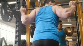 Eignungsturnhalle - muskulöser Mann führt Hocken mit Barbell durch - hintere Ansicht stock video