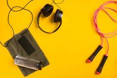 Eignungszubehör auf einem gelben Hintergrund Springseil, Flasche Wasser, Tuch und Kopfhörer stockfoto