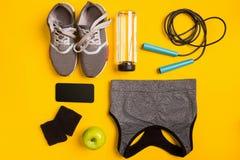 Eignungszubehör auf einem gelben Hintergrund Turnschuhe, Flasche Wasser, Apfel und Sport übersteigt lizenzfreie stockfotos