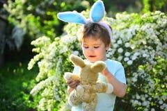 Eijacht op de lentevakantie Konijnjong geitje met konijntjesoren Hazenstuk speelgoed Weinig jongenskind in groene bosliefde Pasen stock foto's
