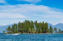 Eiland met bergmening over Meer Met platte kop Montana Stock Foto