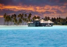 Eiland in oceaan, overwater villa's bij de tijdzonsondergang Stock Afbeeldingen