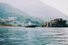Eiland Sveti Stefan met een nabijgelegen jacht royalty-vrije stock fotografie