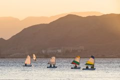 People move in boats with a sail and windsurfing in the Red Sea. Background - the mountains stock photography