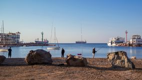 Eilat, The Red sea, fishing. Fishing in Eilat during warm sunrise on the beach of the Red sea wellknown resort with ships, boats and breakwaters stock photo