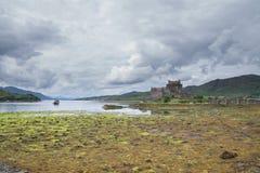 Eilean Donan Castle, Σκωτία at low tide με τους δραματικούς ουρανούς Στοκ Φωτογραφία