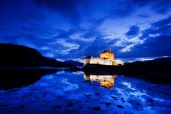 Eilean Donan Castle during blue hour after sunset. Reflecting itself into the water during evening, Loch Duich, Dornie, Scotland, stock image