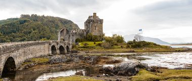 Panorama of Eilean Donan castle with Scottish flag Royalty Free Stock Images