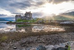 Eilean Donan Castle during sunset while canoes passing by - Dornie, Scotland royalty free stock photos