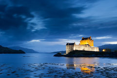 Eilean Donan Castle at twilight, Scotland. Eilean Donan Castle illuminated by decorative lights at twilight and surrounded by Loch Duich Royalty Free Stock Image