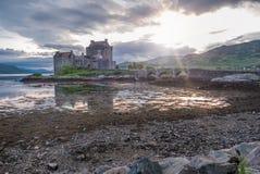 Eilean Donan Castle under solnedgång medan kanoter som förbigår - Dornie, Skottland royaltyfria foton