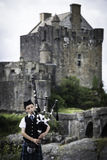 Eilean Donan, UK - August, 2014 - A Scottish piper plays for visitors outside Eilean Donan Castle in the Highlands of Scotland Stock Photography
