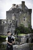 Eilean Donan, UK - Augusti, 2014 - en skotsk pipblåsare spelar för besökare utanför Eilean Donan Castle i Skotska högländerna av  Arkivbild
