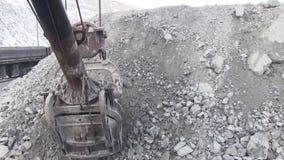 Eimer eines großen Baggers voll des Felsens stock footage