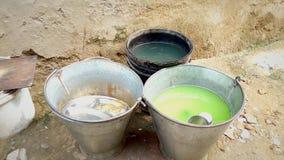 Eimer grünes Wasser und etwas Tonware Stockbilder