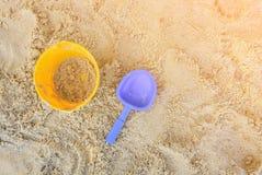 Eimer mit gelbem Sand und blaue Schaufel am Strand Stockfotos