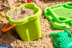 Eimer, Sieb und Formen im Sand im Sandkasten, Kinderspielplatz Stockbild