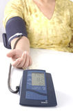 Ein Älterer, der eine Hauptblutdruckprüfung nimmt Stockbilder