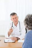 Ein älterer Doktor, der mit seinem Patienten spricht Lizenzfreie Stockfotografie