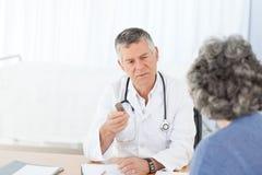 Ein älterer Doktor, der mit seinem Patienten spricht Stockbild