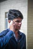 Ein älterer Junge am Telefon Stockbild