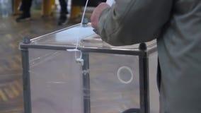 Ein älterer männlicher Wähler setzt den Wahlstimmzettel in die Wahlurne ein Wahl des Präsidenten von Ukraine Wappen ein Emblem stock footage
