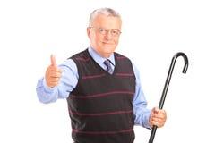 Ein älterer Mann, der einen Stock anhält und Daumen aufgibt Stockbilder
