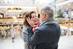 Ein älterer Mann, der einer Frau ein Geschenk im Einkaufszentrum zur Weihnachtszeit gibt stockfotografie