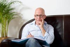 Ein älterer Mann, der Kenntnisse nehmend sitzt Stockfotografie