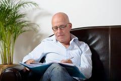 Ein älterer Mann, der Kenntnisse nehmend sitzt Stockfotos