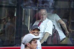 Ein älterer Mann in einem weißen Hemd mit kurzen Ärmeln und eine rote Bindung, die durch das Fenster des Busses schaut Stockfoto