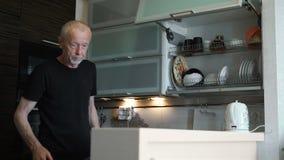 Ein älterer Mann im Ruhestand, verbringt Zeit in der Küche seines Hauses stock video footage