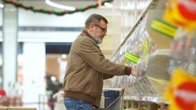 Ein älterer Mann kauft Getreide in der Lebensmittelgeschäftabteilung eines Supermarktes Der Pensionär rollt den Wagen und setzt s stock footage
