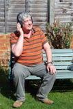 Ein älterer Mann mit drahtlosen Kopfhörern. Stockfoto