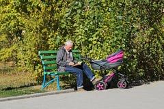 Ein älterer Mann mit einem Baby im Spaziergänger sitzt in einem Park und liest ein Buch Stockfotografie