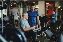 Ein älterer Mann mit einem jungen Trainer, der Stärketrainingsübung in der Turnhalle tut stockbild
